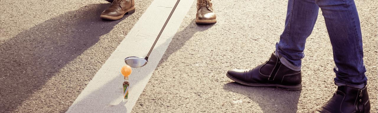 Zwei Personen spielen Golf mithilfe einer Kuemmerling-Flasche